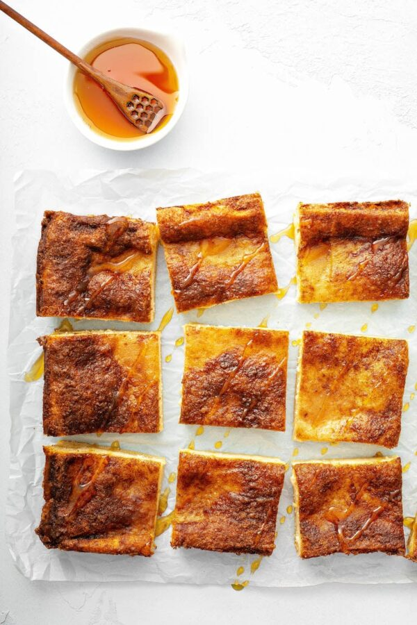 Sopapilla Cheesecake bars sliced into squares with honey on top.