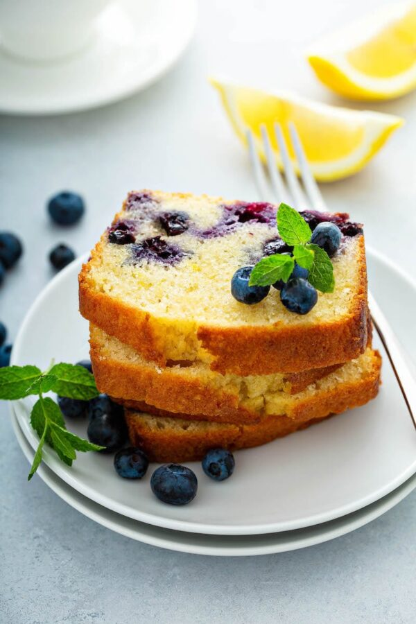 Buttermilk Blueberry Bread stacked on a white plate.