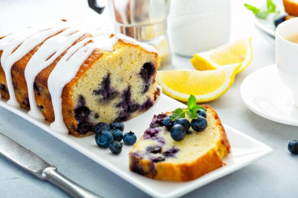 Buttermilk Blueberry Bread drizzled with citrus glaze on a plate.