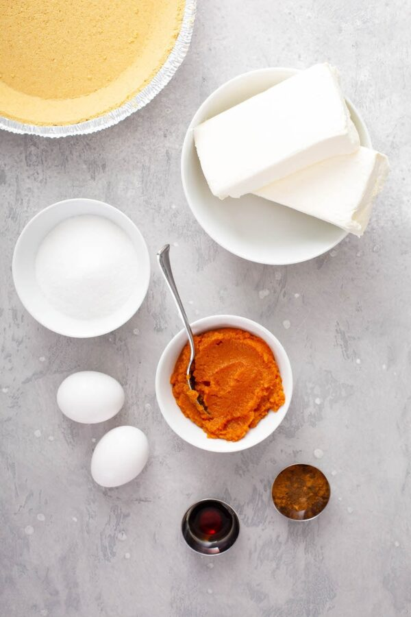 Ingredients for Pumpkin Pie Cheesecake in bowls.
