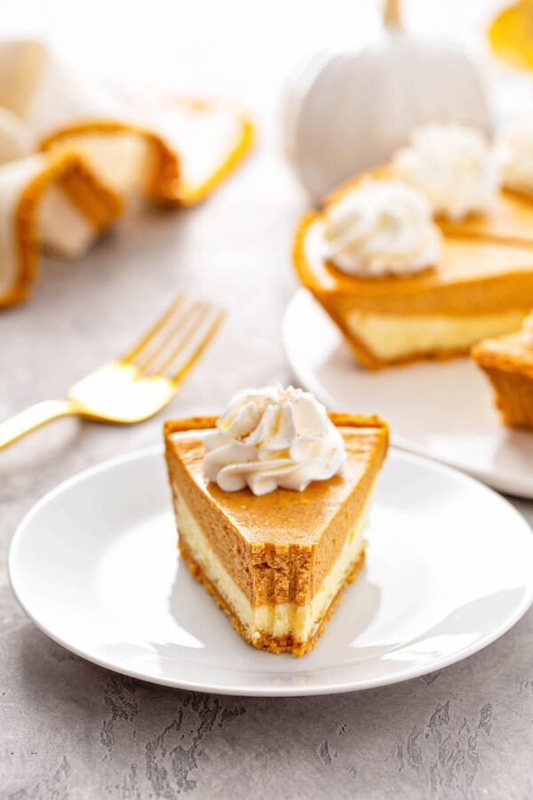 A slice of Pumpkin Pie Cheesecake with bite taken out of it.