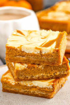 Pumpkin Cheesecake Bars stacked on top of each other.