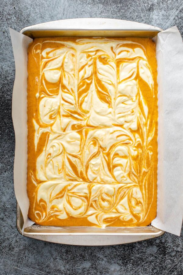 Swirled Pumpkin Cheesecake Bars in a baking pan before baking.