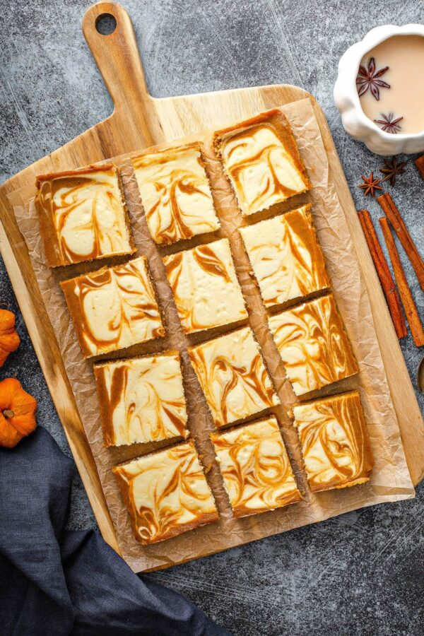Overhead image of pumpkin bars with cheesecake swirled through them on parchment paper.