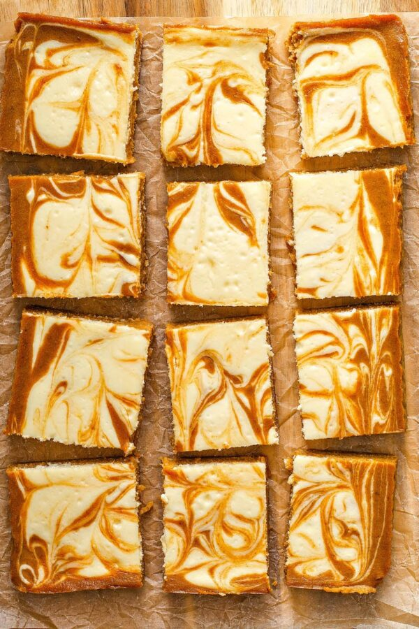 Pumpkin Cheesecake Bar recipe sliced into squares on parchment paper.
