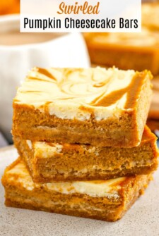 Stacked pumpkin cheesecake bars on a plate.
