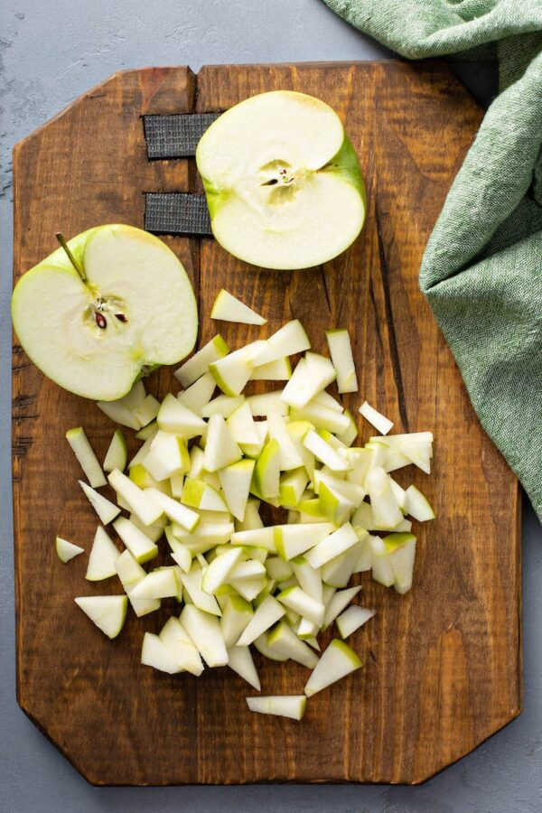 Diced apples on a chopping board for apple pie bombs.