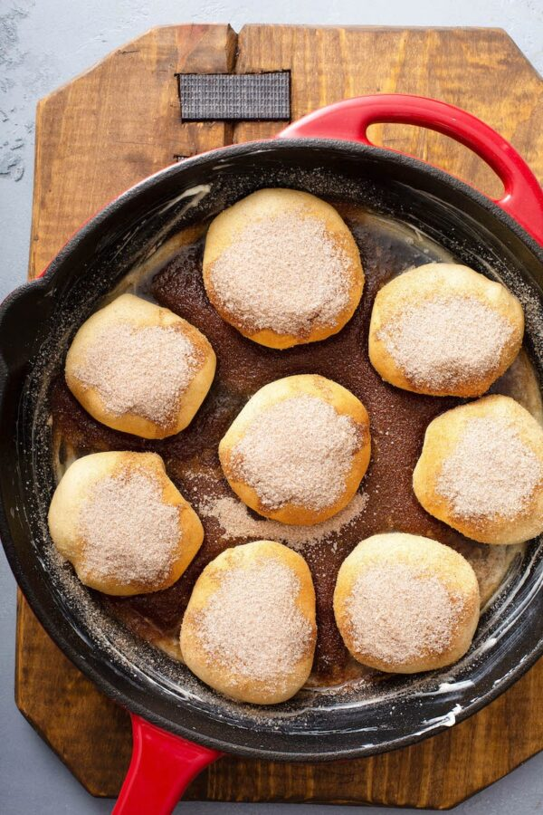 Apple Pie Bombs in skillet before baking with cinnamon sugar topping.