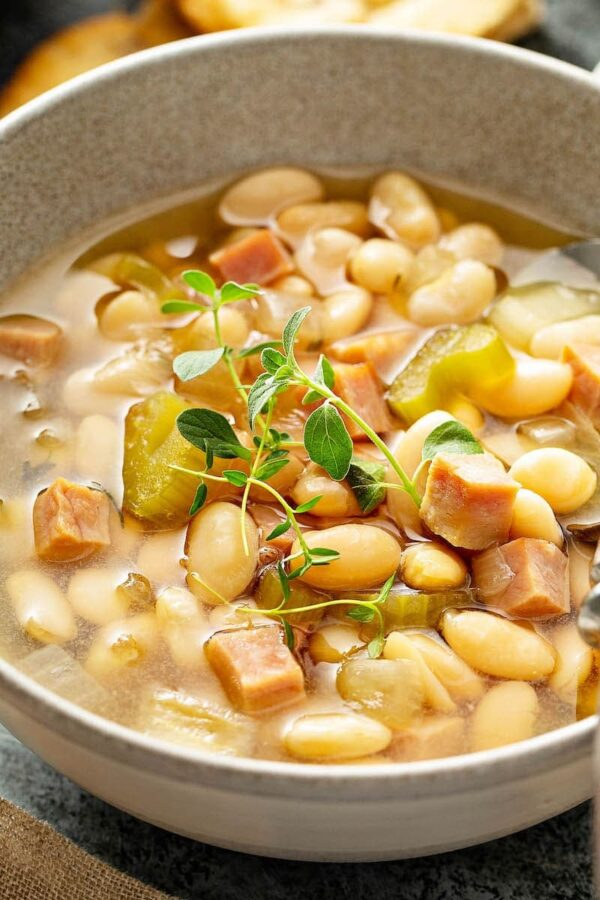 Slow Cooker Ham and Bean sou pin a white bowl.