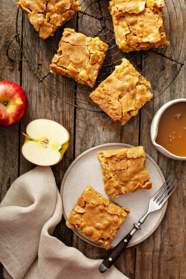 Apple Blondies on a cutting board with fresh apples and caramel.
