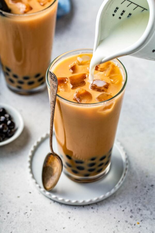 Bubble tea in a glass jar with tapioca pearls in the bottom and cream being poured on top.