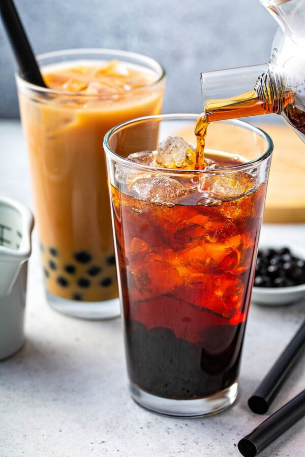 Tea for bubble tea being poured into a glass.