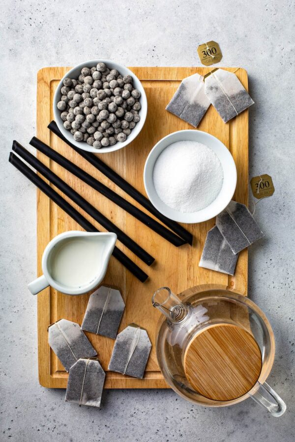 Ingredients to make bubble tea on a cutting board.