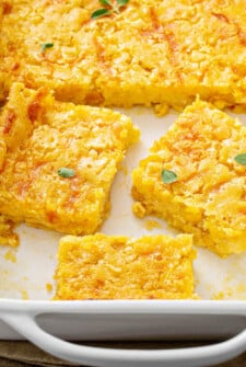 Corn Casserole sliced into squares in a casserole dish.