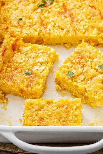 Corn Casserole sliced into squares in a casserole dish.