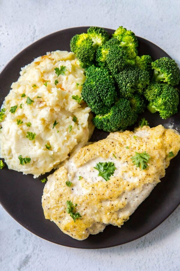 Creamy Parmesan Chicken breasts on a plate with broccoli and mashed potatoes.