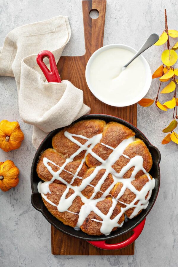 Pumpkin PIe Bombs in a cast iron skillet with cream cheese drizzle.