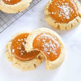 Salted Caramel Cookies topped with flaky sea salt - one cookie has a bite taken out of it.