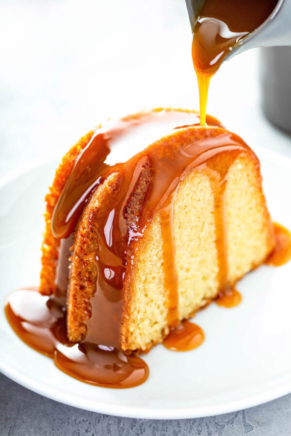 Butterbeer Pound Cake drizzled with butterscotch sauce on a white plate.