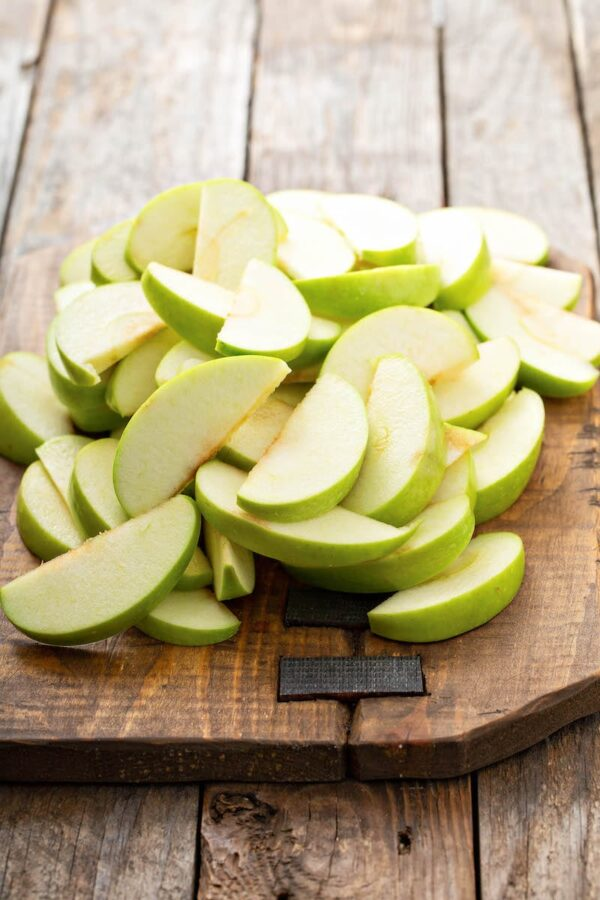 Green apples sliced on a wood cutting board for Fried Apples.