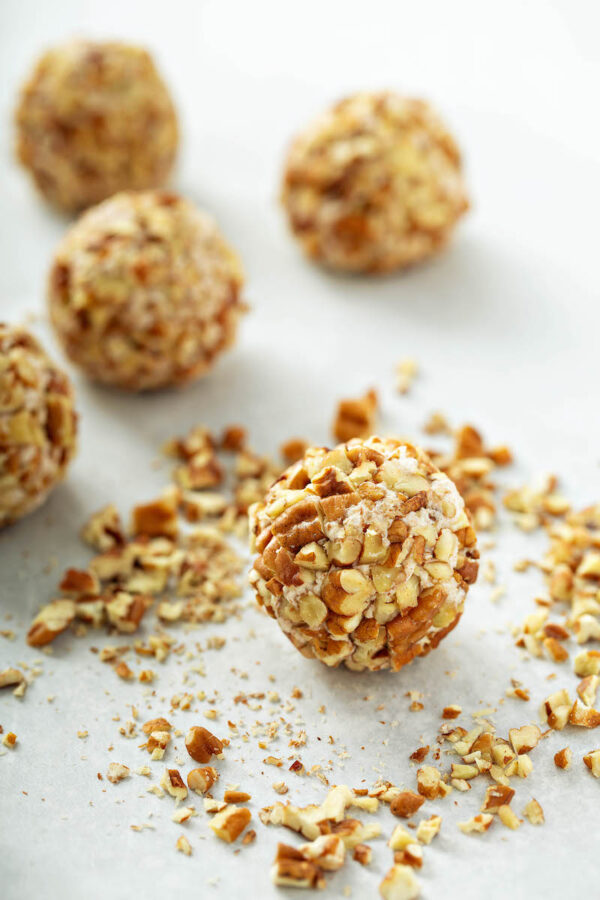 Honey Pecan Cheese Ball Recipe on parchment paper after rolling in pecans.