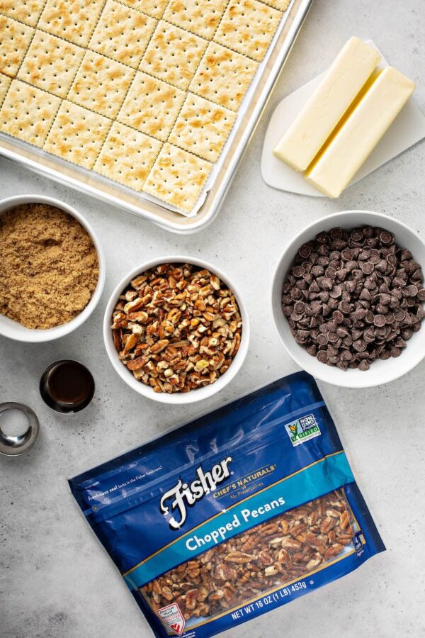 Saltin crackers, sugar, pecans, chocolate and butter on a counter.