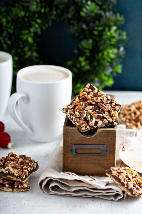 Pecan Christmas Crack in a box with a cup of coffee.