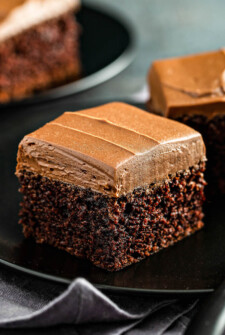 Chocolate Mayonnaise Cake on a black plate with fluffy whipped chocolate icing on top.