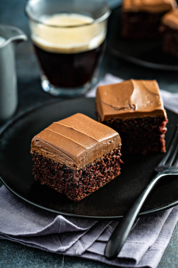 Two slices of Chocolate Mayonnaise Cake on a black plate with a fork.