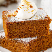Gingerbread stacked in two big thick slices with whip cream on top.