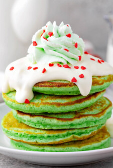 Green Grinch Pancakes on a plate with cream cheese toppings.