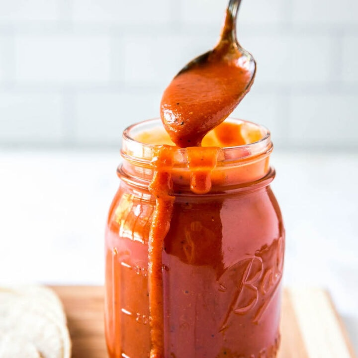 Homemade enchilada sauce recipe in a jar with a spoon scooping some out.