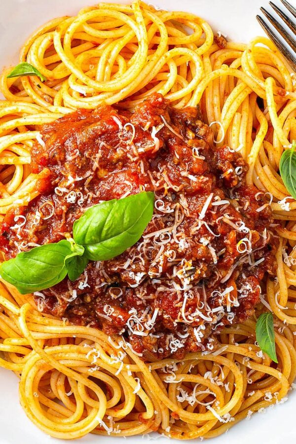 Up close image of bolognese sauce over spaghetti noodles.