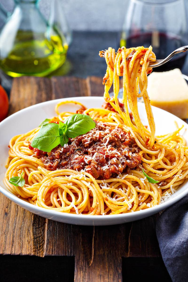 Spaghetti bolognese in a bowl with a fork taking a bite out of it.