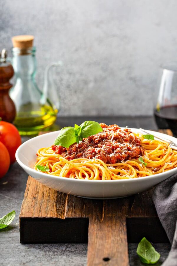 Bolognese sauce over spaghetti in a white bowl.