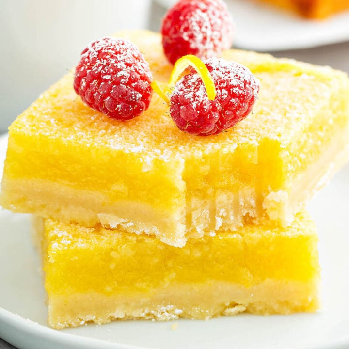 Lemon Bars stacked on top of each other on a white plate with a bite taken out of one.