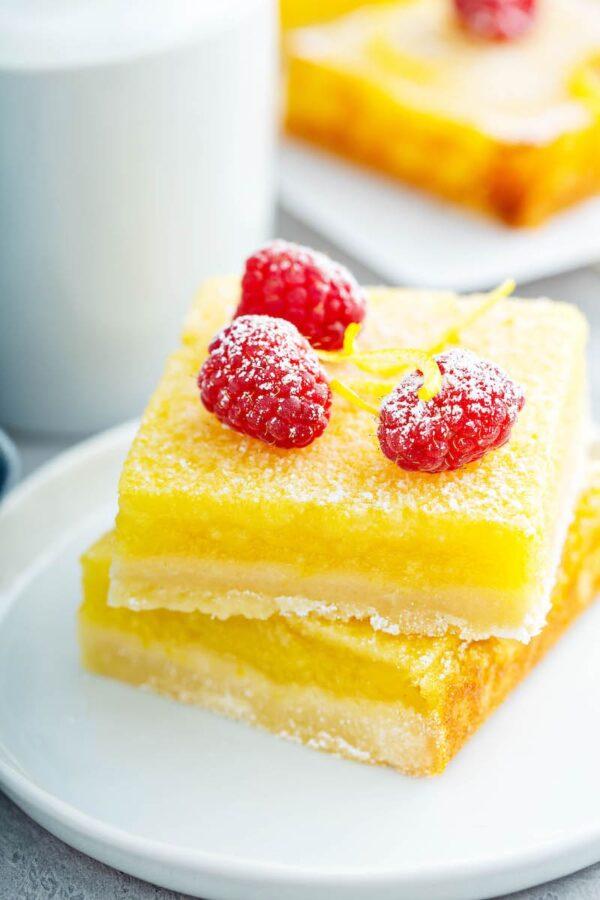 Two lemon bars on a white plate.