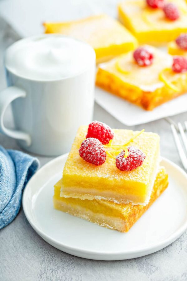 Lemon Bars stacked on a white plate with powdered sugar on top.
