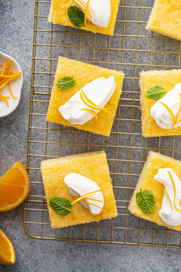 Slices of orange coconut cake cut into squares with whip cream.