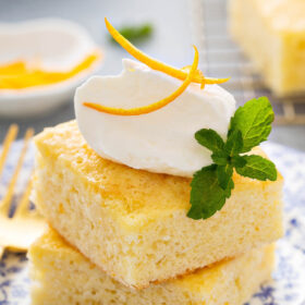 Two pieces of Southern Orange Coconut Cake topped with whipped cream on a blue and white floral plate