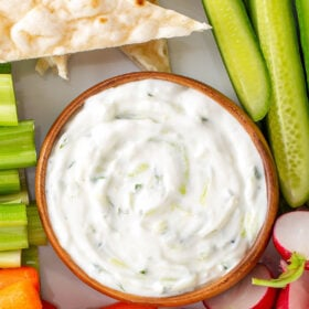 A bowl of Greek Tzatziki Sauce surrounded by carrots, celery, pita bread and other foods for dipping