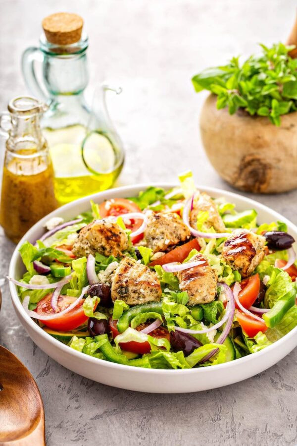 This easy Greek salad recipe is packed with colorful tomatoes, peppers, red onions. Topped with creamy feta crumbles and homemade Greek salad dressing! #GreekRecipes #Greek #GreekSalad #SaladRecipes #Salad #Healthy #HealthyRecipes #GreekSaladDressing #HomemadeSaladDressing #SaladDressingRecipes #LowCarb #LowCarbRecipes #LunchRecipes #KetoRecipes