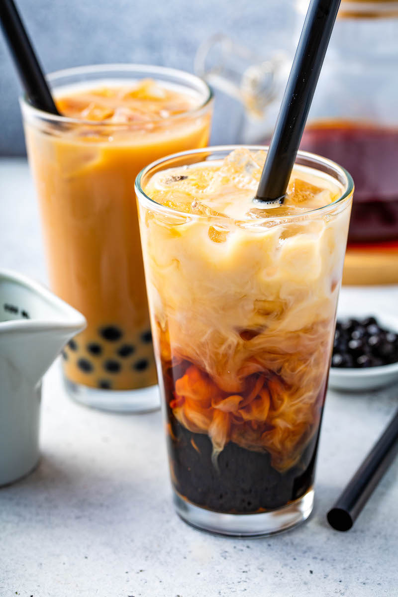 Bubble Tea being mixed together with cream in a glass with ice.