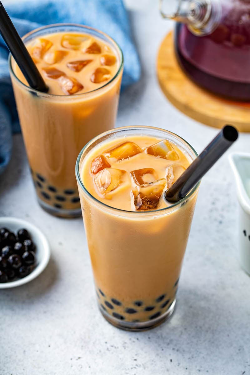 Up close image of Bubble Tea in a clear glass with ice on top and a black straw.