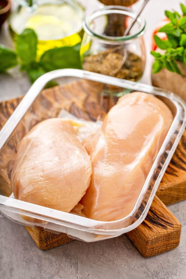 Raw chicken breasts in a glass tupperware