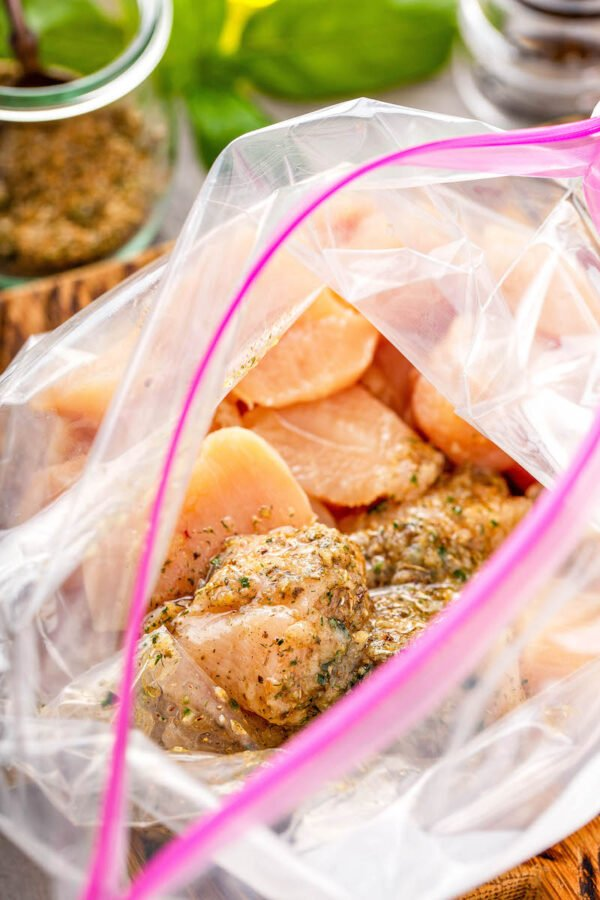 Top view of a ziploc bag with raw chicken breasts and spices