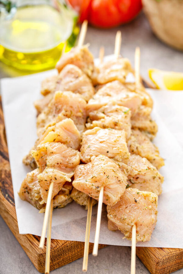 Stacks of wood skewers with pieces of marinated raw chicken breasts on them.