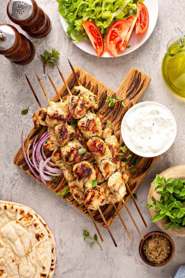 Top view of wood skewers with cooked chicken souvlaki on a wooden tray next to dipping sauce and herbs.