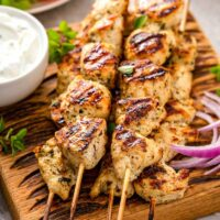 Stack of wooden skewers with cooked chicken souvlaki next to a bowl of dipping sauce