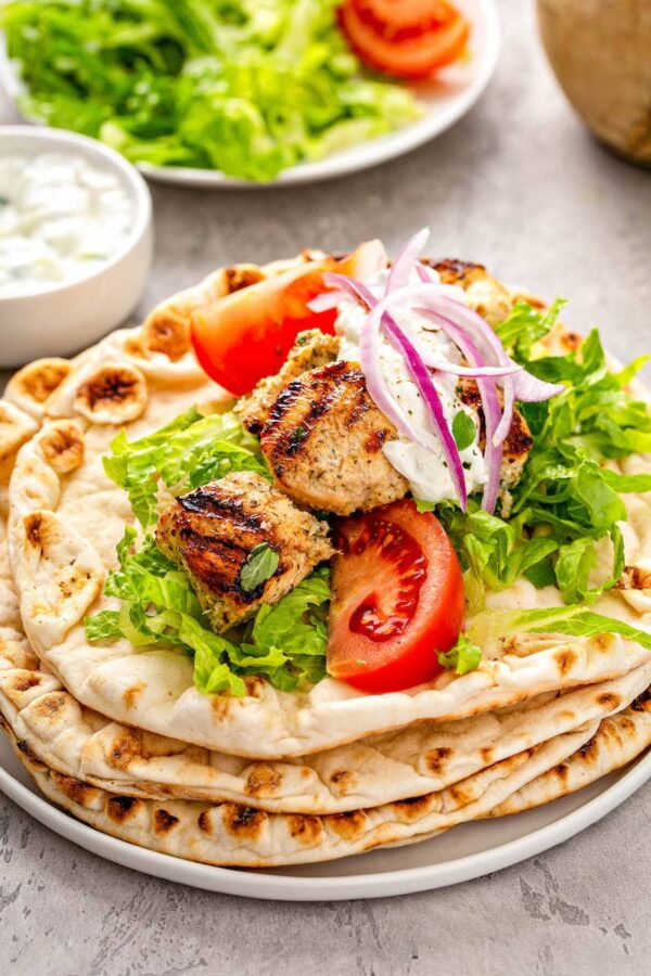 Chicken souvlaki with tomatoes, lettuce and tzatziki sauce on a stack of warm pita bread